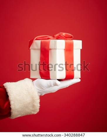 White box bound with red ribbon offered by Santa