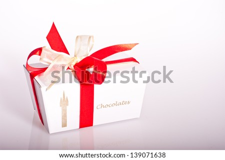 White box of chocolates with red and white ribbon on its reflection - stock photo