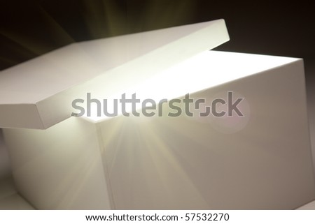 White Box with Lid Revealing Something Very Bright on a Grey Background. - stock photo
