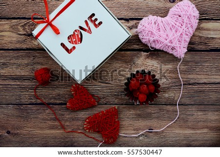 white box with the word love inside with cakes, decorations of hearts of the thread. Surprise to Valentine's Day