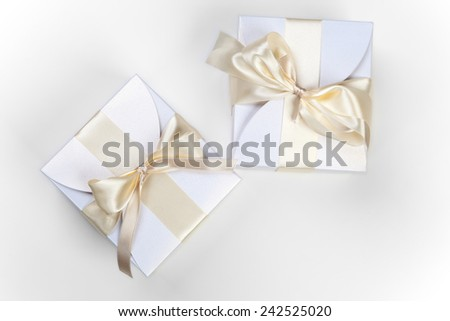 White boxes with gold ribbon on white  - stock photo