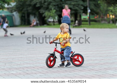 white boy with blond hair and blue jeans is riding on his red children's bike in a city park. Security and protection of children in the performance of tricks on the bike. Looking back into the past.