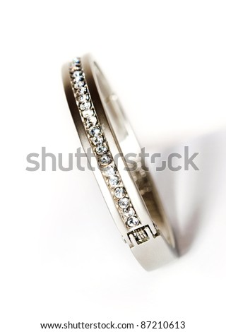 white bracelet with diamonds on a white background, vertical - stock photo
