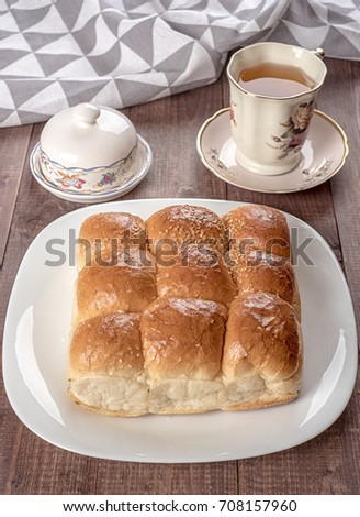 White bread in glass plate, napkin, butter dish and cup of tea on wooden table