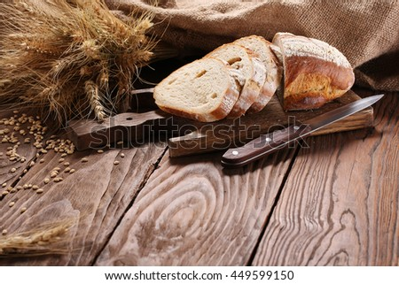 white bread on a cutting board, rye ears on the background of wooden boards - stock photo