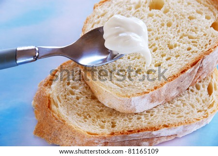 white bread slices with soft butter on spoon closeup - stock photo