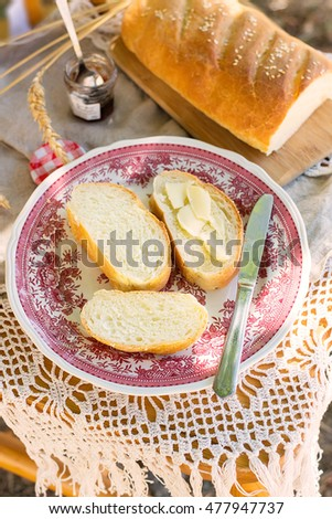 White bread with butter for breakfast in the garden. Selective focus
