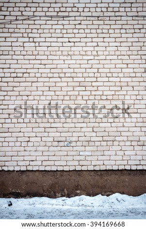 White brick wall and a ground covered with snow