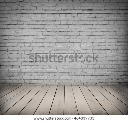 White brick wall and wooden floor. Dark room interior