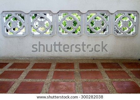 White brick wall with air vents. Wash sandstone interspersed with tiles on the floor. - stock photo