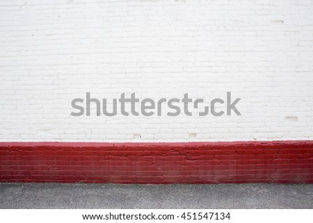 white brick wall with red strip on street - stock photo