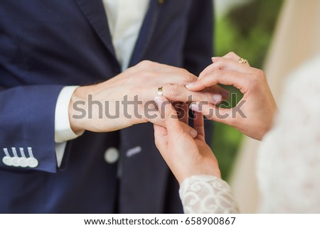 White bridal couple at wedding ceremony outdoors. Closeup of young happy beautiful bride and handsome groom holding hands and exchanging golden rings. Horizontal color picture.