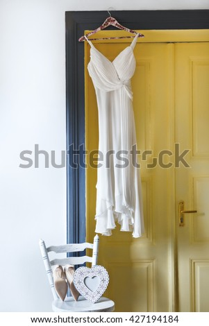 White bridal dress hanging on peg near brown door. Shoes and white heart lying on chair. No people, indoor, interior - stock photo