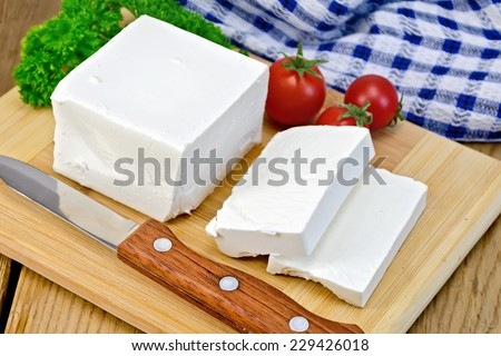 White brine cheese, knife, parsley, tomatoes, napkin on a wooden boards background - stock photo