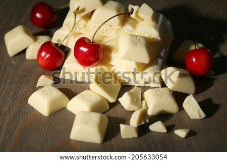 White broken chocolate bar and fresh cherries, on color wooden background