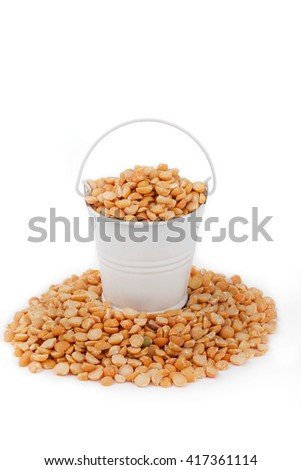White bucket full of peas, stands on a heap peas, on a white background