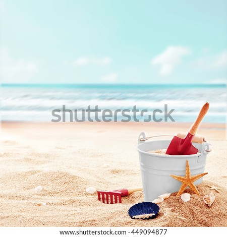 White bucket with red shovel and rake on clean empty beach near beautiful ocean on a pleasant day