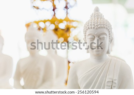 white buddha figure in bokeh. - stock photo