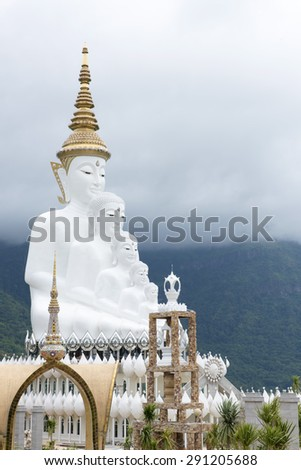 White buddha statue, Wat Phra That Pha Son Kaew, during the rainy season. - stock photo