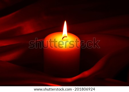 White burning candle on a small dark background.