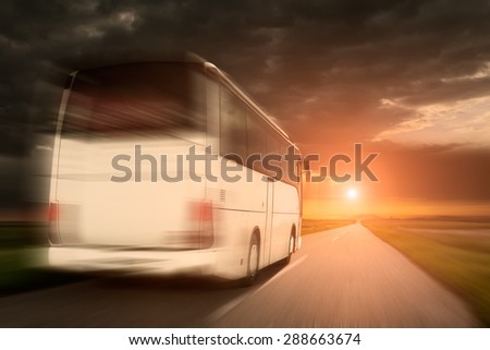 White bus in fast driving on an empty open road towards the setting sun in blurred motion. - stock photo