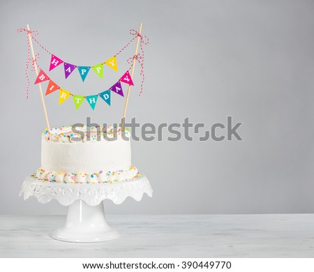 White Buttercream birthday cake with colorful bunting and sprinkles over white background - stock photo