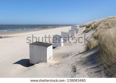 White cabins (or beach houses) standing against the grass covered dunes on a deserted beach at Domburg in Holland. - stock photo