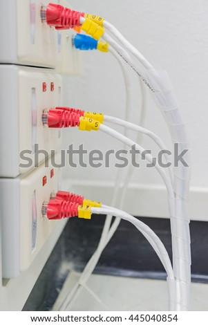 White cable with red and blue RJ-45 connector is connected to a wall outlet. White cable is connected to a wall outlet. The cable is white color and the socket is light cream color.