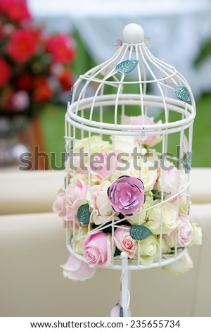 White cage with natural roses as decoration on wedding  - stock photo