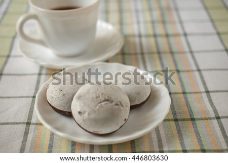 White cake in the foreground and a Cup of coffee - stock photo