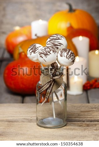 White cake pops decorated with dark chocolate. Orange pumpkins in the background. Halloween party setting.  - stock photo