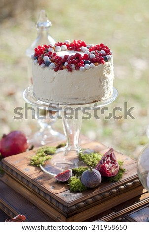 White cake with red berries for the bride and groom - stock photo