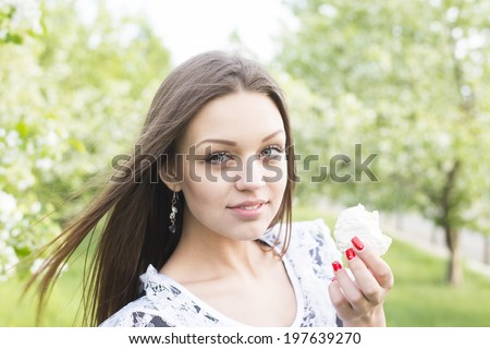 White cakes - zephyr  Beautiful girl eating cupcake outdoor on green spring park background  Young adult woman enjoying and eat unhealthy food snack in lunch break smiling happy. - stock photo