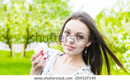 White cakes - zephyr Beautiful girl eating cupcake outdoor on green spring park background Young woman enjoying and eat unhealthy food snack in lunch break smiling happy.Copy space for inscription - stock photo