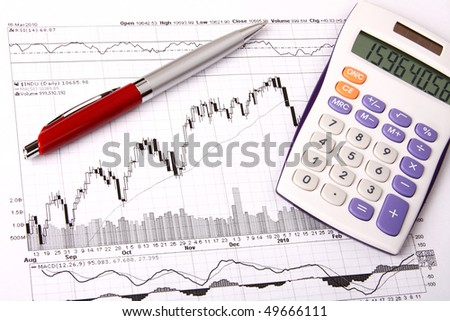 White calculator and a red pen lying on a financial chart
