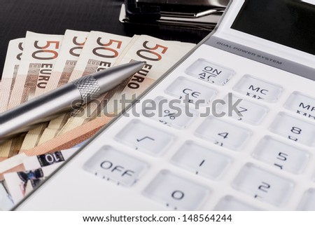 White calculator on top of euro banknotes on black clipboard with silver pen