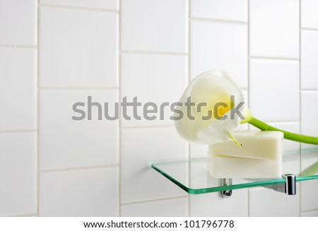 White calla on glass shelf with soap in bathroom. - stock photo