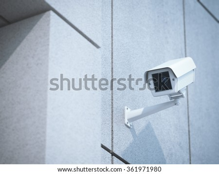 White camera on the concrete office wall - stock photo
