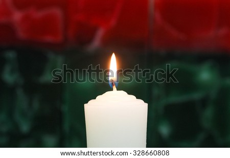 White candle burning with red and green holiday texture background - stock photo