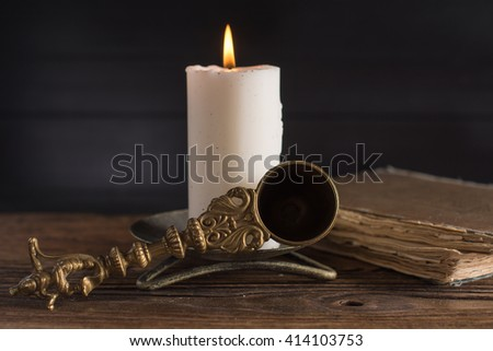 White candle, candle snuffer and and old book with yellow pages.