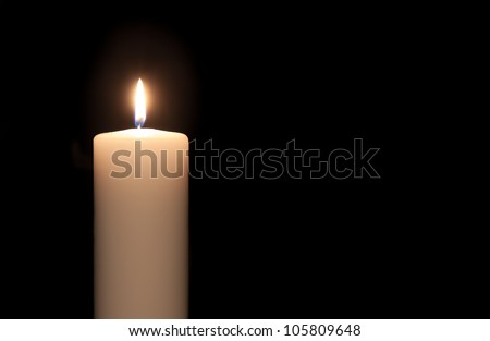 White candle isolated against a black background - stock photo