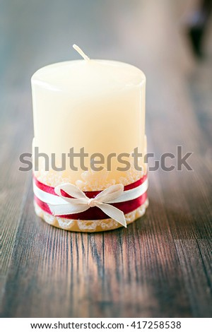 White candle with bow on Wood Background - stock photo