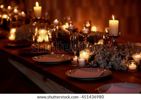 White candles burn over white dinner plates on the dinner table - stock photo