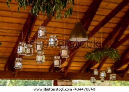 white candles in glass jars hanging from the ceiling - stock photo