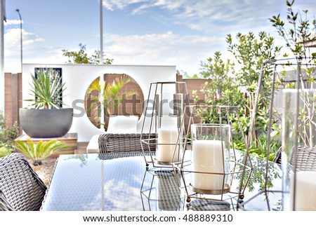 White candles on a glass table under a sunlight view from outdoor like a patio or dining area, the background is blurred and rattan chairs can be seen closely