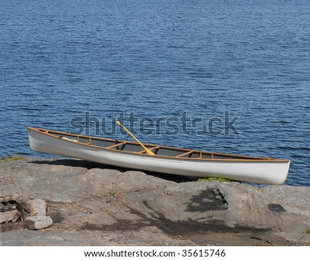 White canoe on rocky shore
