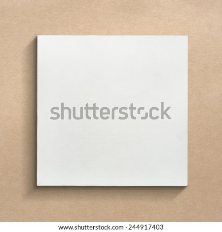 White canvas frame on brown paper sheet background.