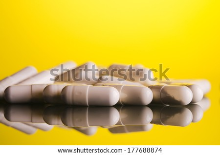 white capsule on glass yellow background
