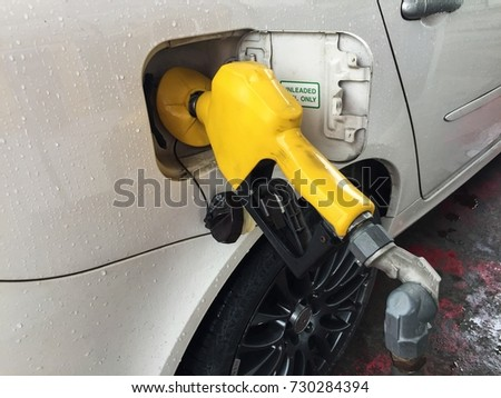 White Car Natural Fuel being filled with yellow nozzle at petrol station.