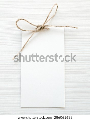 White card note with ribbon on wooden background
